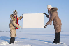 Girls holding white poster. At winter snowy field Royalty Free Stock Photos