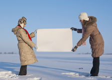 Girls holding white poster. At winter snowy field Stock Photo