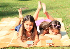 Girls with houses. Two lying little barefoot girls playing with small houses stock photo