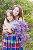 Girls hug holding flower Lilacs Stock Images
