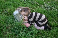 Girls hugging. Sisters sitting in a meadow, hugging each other Royalty Free Stock Photos