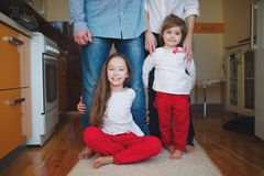 Girls hugging mom and dad for legs Stock Photography