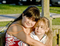 Girls hugging outdoors. Happy young Asian girl hugging preschool friend outdoors Stock Photos