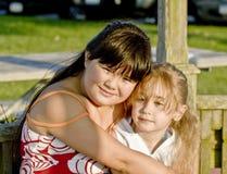 Girls hugging outdoors Stock Photos