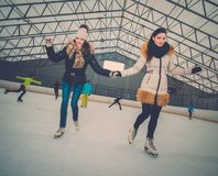 Girls on ice-skating rink. Two girls on ice-skating rink royalty free stock images