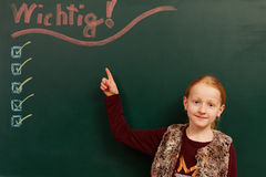 Girls and important list on the board. Young girl looking up to the chalkboard royalty free stock photography