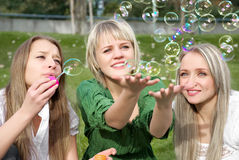 Girls inflating soap-bubbles Stock Photos