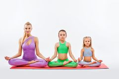 Hatha yoga fitness . Young mother Instructor and daughters exercise gymnastic together. Isolated on white background Royalty Free Stock Images