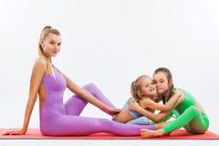 Hatha yoga fitness . Young mother Instructor and daughters exercise gymnastic together. Isolated on white background Royalty Free Stock Photo