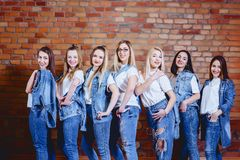 girls in jeans at background of brick wall stock images