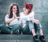 Girls in jeans and a white T-shirt. Two girls in jeans and a white T-shirt, against the wall background, the concept of urban clothing, female friendship and stock image
