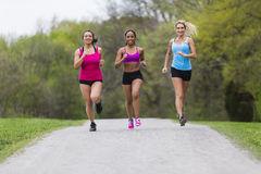 3 Girls Jogging. Three young women jogging in a park royalty free stock photo