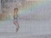 A girls joyfully runs and bathes in the city`s fountain in the rays of the rainbow. Hot sunny weather. Children`s carefree game in royalty free stock photo