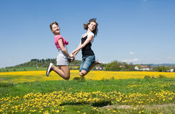 Girls jump. Happy girls jump in field under blue sky Stock Images