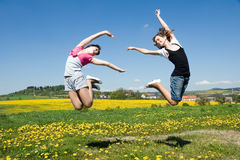 Girls jump. Happy girls jump in field under blue sky and clouds Royalty Free Stock Photography