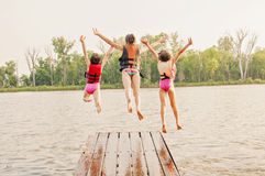 Girls jump into lake off dock. Three girls wear life jackets, and jump off boating dock into lake Royalty Free Stock Photography