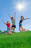 Girls jump on the meadow. Against blue summer sky Royalty Free Stock Image