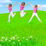 Girls jump on a meadow Stock Photo