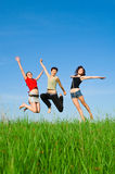 Girls jump on the meadow Stock Photos