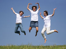Girls jumping. Three girls jumping against a deep blue sky royalty free stock photography