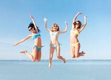 Girls jumping on the beach Stock Image