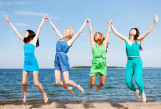 Girls jumping on the beach Royalty Free Stock Photos