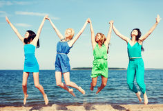 Girls jumping on the beach Stock Images