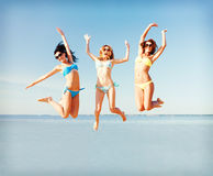 Girls jumping on the beach Stock Photos