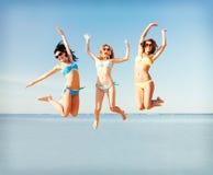 Girls jumping on the beach Stock Photos