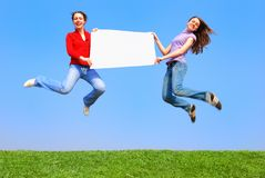 Girls jumping with blank sheet Royalty Free Stock Photo
