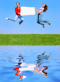 Girls jumping with blank sheet Royalty Free Stock Photography