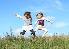 Girls jumping in grass Stock Images