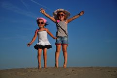 Girls jumping on the sandy beach. Friends Stock Images