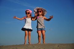 Girls jumping on the sandy beach Stock Photography