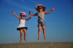 Girls jumping on the sandy beach. Friends Royalty Free Stock Photos