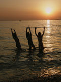 Girls jumping in the sea in sunset. Three girls (best friends) are having fun jumping in the Adriatic sea at wonderful colors at sunset . Vertical color photo Royalty Free Stock Photography
