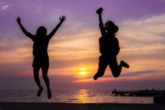 The girls jumping silhouette at the sea stock photo