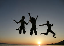 Girls jumping in sunset. Three young twins, (best friends) sisters jump, enjoy in golden twilight in summer holidays at Adriatic sea (Croatia - Dalmatia) Stock Photos