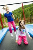 Girls Jumping on Trampoline. Happy girls jumping high on a trampoline on a sunny day outdoors Royalty Free Stock Image