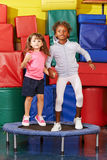 Girls jumping on trampoline in preschool Royalty Free Stock Images