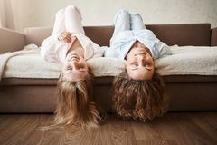Girls just wanna have fun. Beautiful girlfriends lying on sofa upside down with hair touching floor, wearing cozy royalty free stock photography