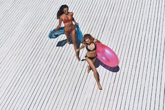 Girls just want to have fun. Top view of two beautiful young women in bikini smiling while running outdoors Royalty Free Stock Image