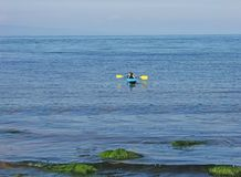 Girls in Kayaks in Irish Sea at Cushendun Co. Antrim Northern Ireland. Girls in Kayaks on Irish Sea at Cushendun Co. Antrim Northern Ireland stock image