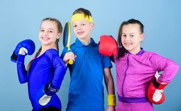 Girls kids with boxing sport equipment and boy tennis player. Ways to help kids find sport they enjoy. Sporty siblings. Friends ready for sport training. Child stock image