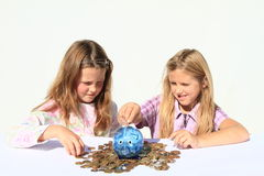Girls - kids filling saving pig with money. Concentrated girls - smiling kids filling blue saving pig with money - savings of czech crowns Stock Photography