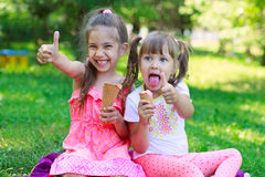 Girls kids sisters friends teasing eating ice cream. Girls kids sisters friends teasing showing off  tongues, sitting on grass, eating ice cream thumb up, focus Royalty Free Stock Images