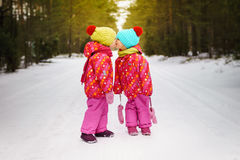 Girls and kiss in winter forest. Two girls kissing on a snowy road in the woods Royalty Free Stock Photo