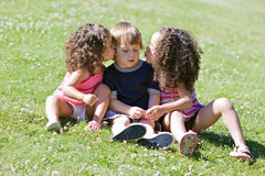 Girls kissing boy on cheek Royalty Free Stock Images