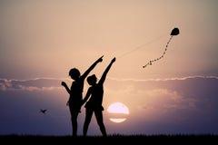 Girls with kite at sunset Stock Photos