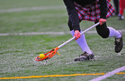 Girls lacrosse ball pick. High school girls varsity lacrosse player scoops up the ball on a rain drenched turf field royalty free stock photos